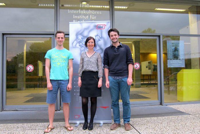 BU: Christian Maas, Christine Decker und Benjamin Schröder, Sprecher des jGBM vor dem Interfakultären Institut für Biochemie, IFIB