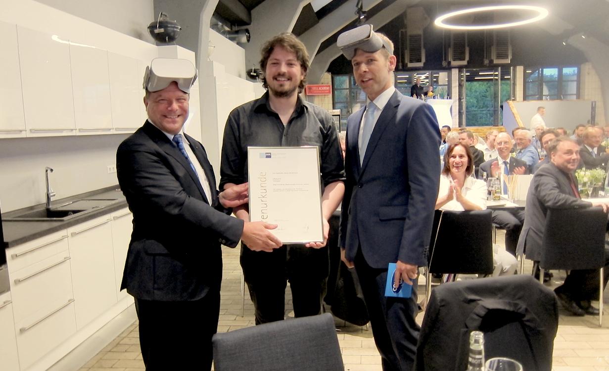 IHK-Präsident Christian O. Erbe überreicht Philipp Zajac von RehaGo seine Auszeichnung. Auch Moderator Helge Thun setzt die VR-Brille auf
